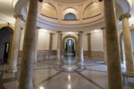 The beautiful Rotunda with large marble columns and a view of the circular arches on the second floor.
