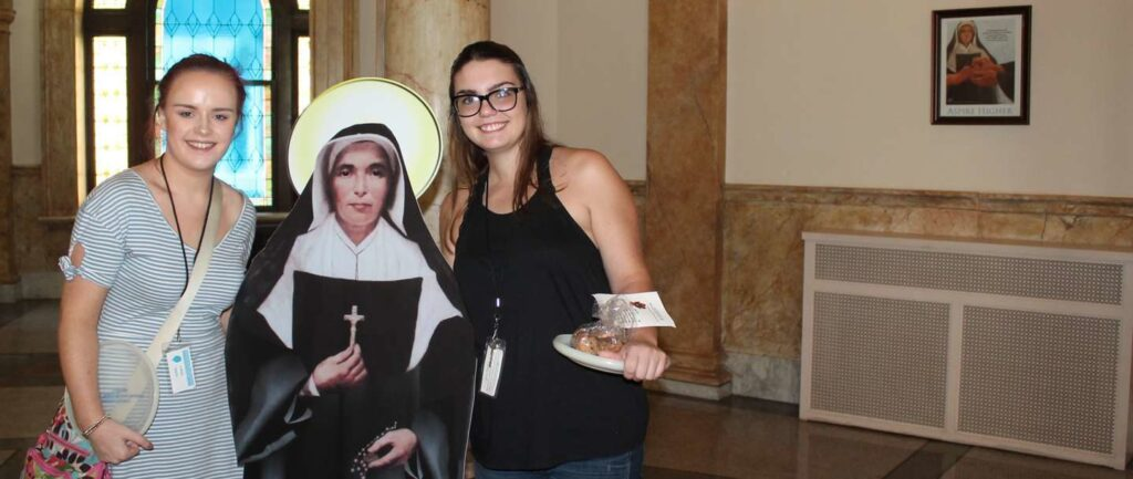 Two female student on each side of Flat Saint Mother Theodore Guerin smiling.