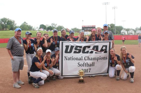 A photo of the SMWC softball team with the National Championship banner and trophy.