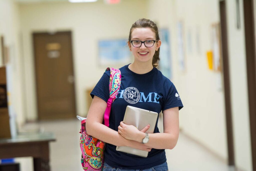 A female student holding her ipad and bookbag smiling.