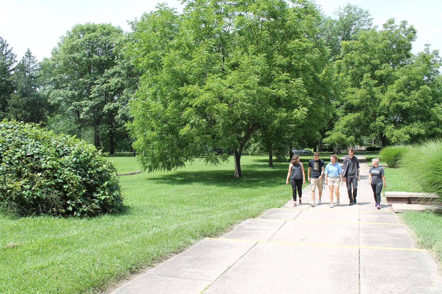 Three female and two male students walk together down the sidewalk in front of Le Fer Hall.