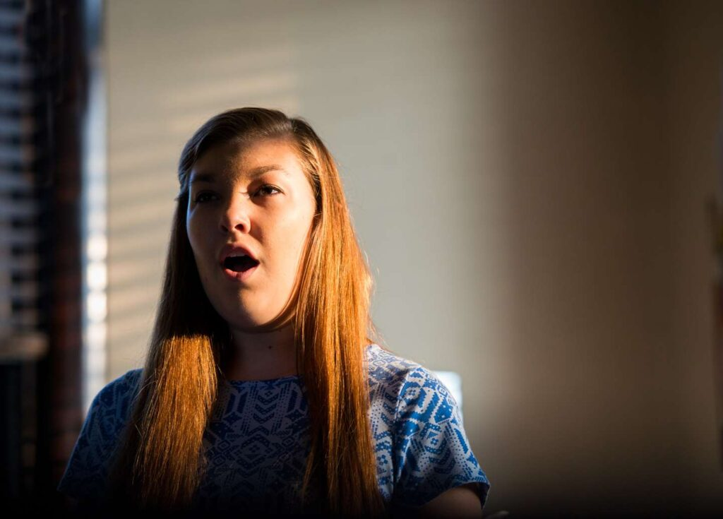 A female student practicing during voice lessons as the sun shines through the window on her face.