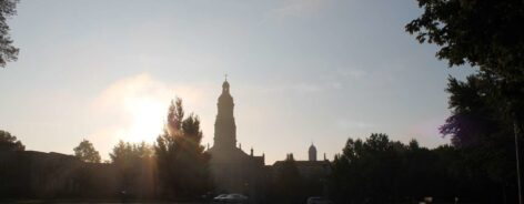 The sun rising up over the trees with the silhouette of the Chuch of the Immaculate Conception.