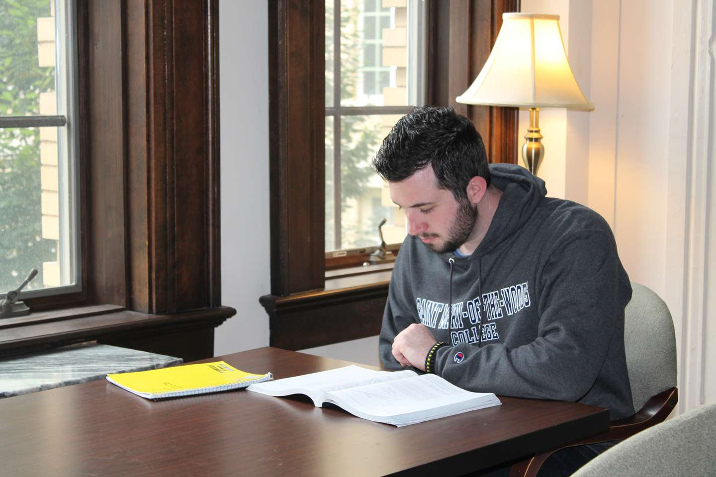 A male student studys in the Sullivan Parlor near a window overlooking the campus.