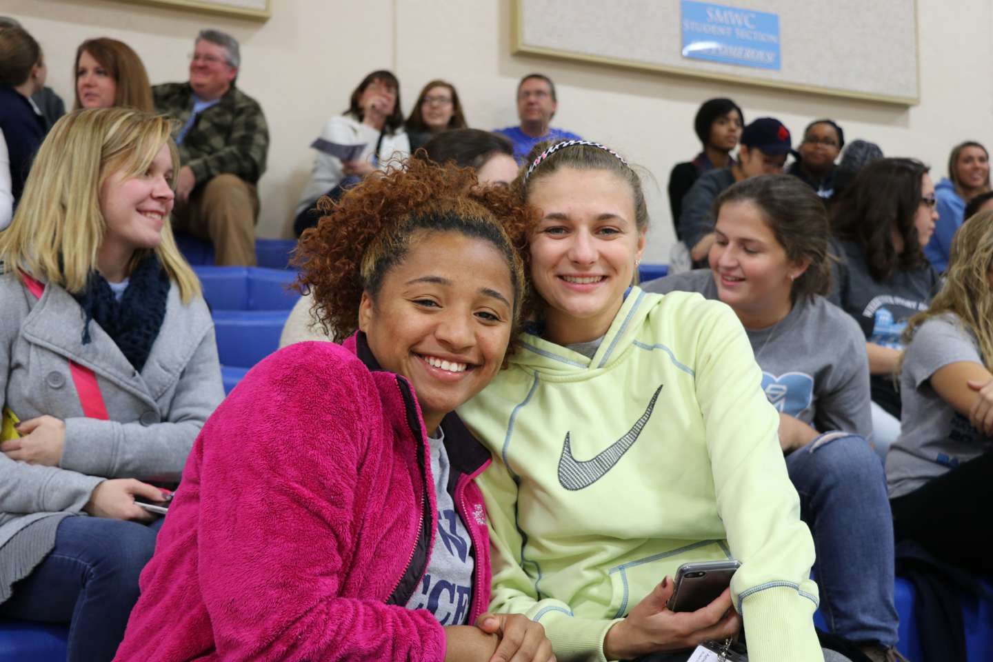 Two friends sitting in the bleachers, holding a phone and smiling.