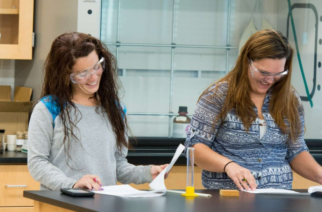 Two female students smiling as they work on a chemistry assignment together.