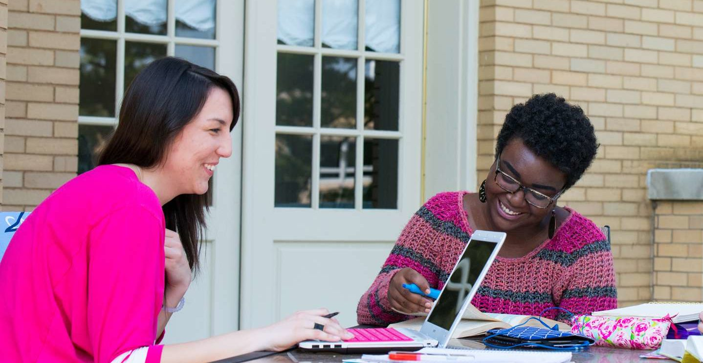 Two students smiling as they study together on the patio outside Le Fer Hall.