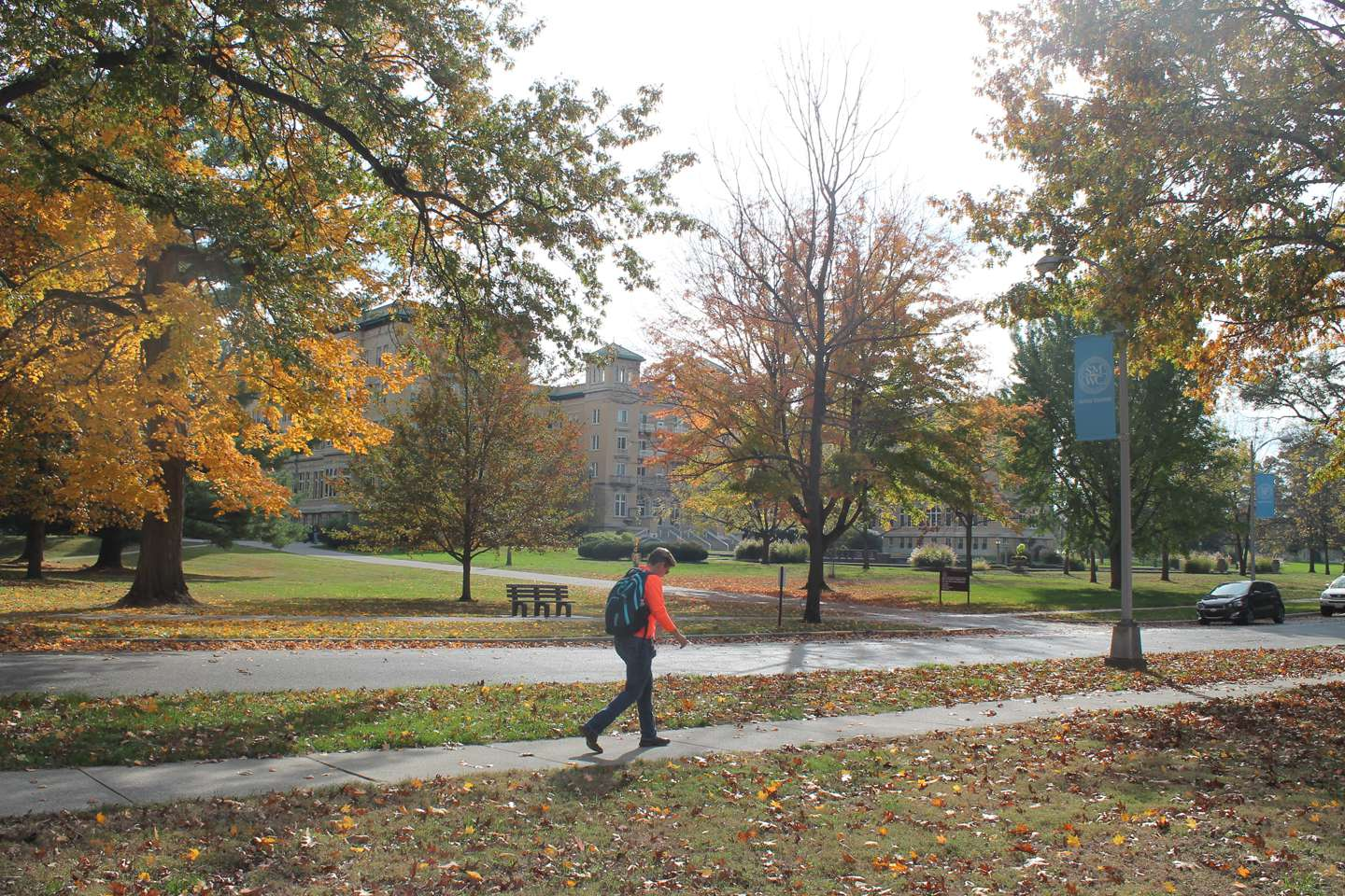 A student walks across campus with the fall leaves and Le Fer Hall in the background.