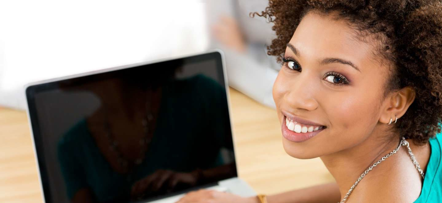 A female smiling with her laptop.