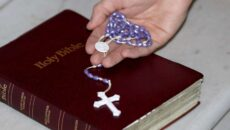 A photo of someone holding a rosary with a Holy Bible.